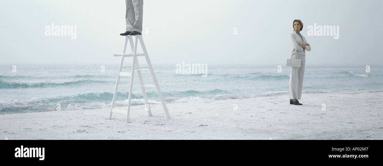 Woman standing on beach with arms crossed, looking toward man standing on ladder - Stock Image