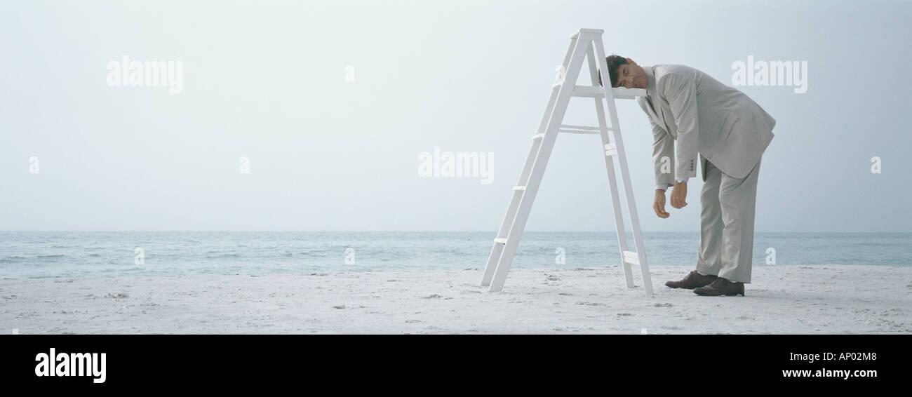 On beach, businessman sleeping standing up, resting head on ladder - Stock Image