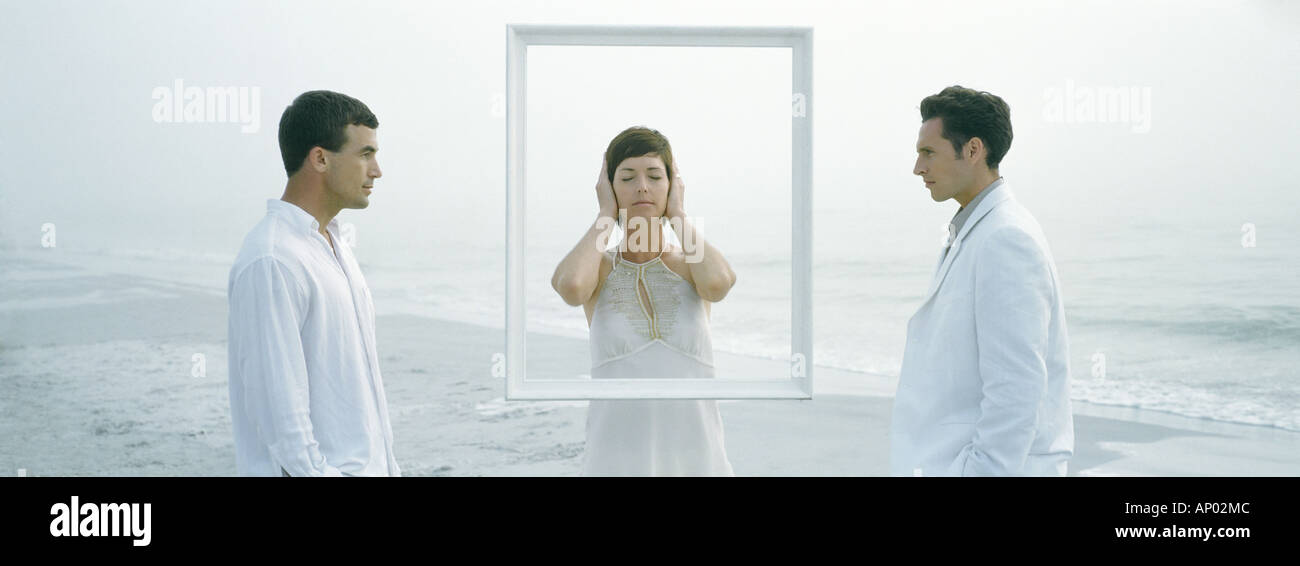 Woman standing behind frame, eyes shut and ears covered, between two men - Stock Image