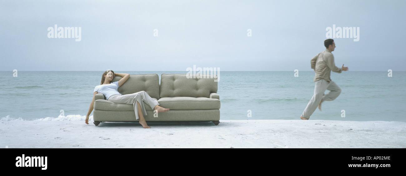 On beach, woman reclining on sofa while man runs away - Stock Image