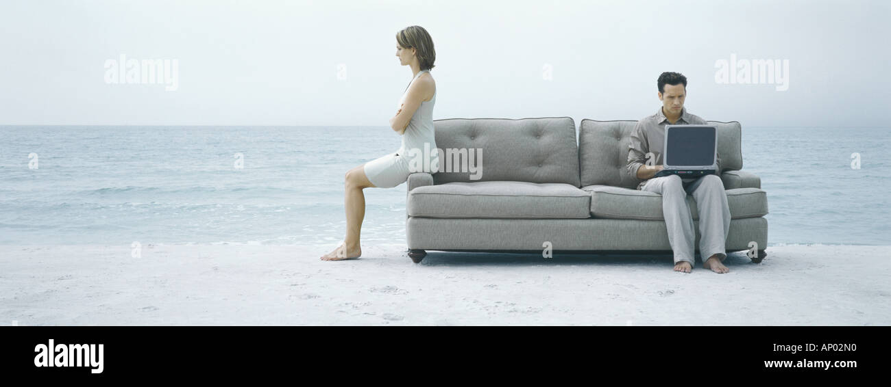 On beach, man using laptop on sofa while woman turns back to him - Stock Image