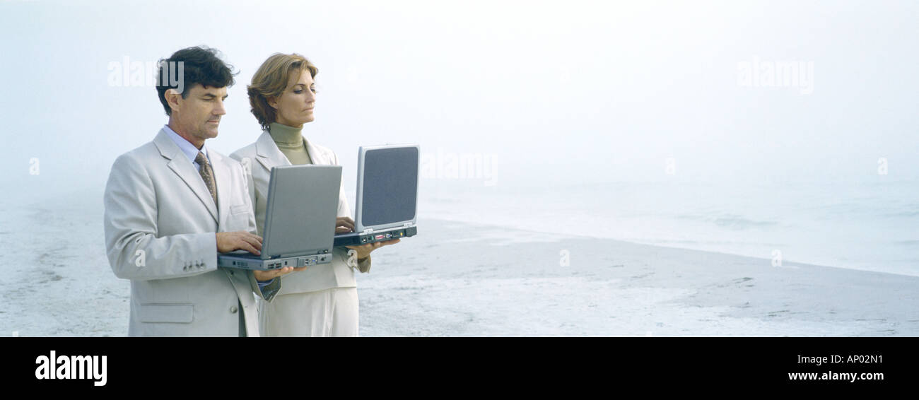 Businessman and woman standing, holding laptops on beach - Stock Image