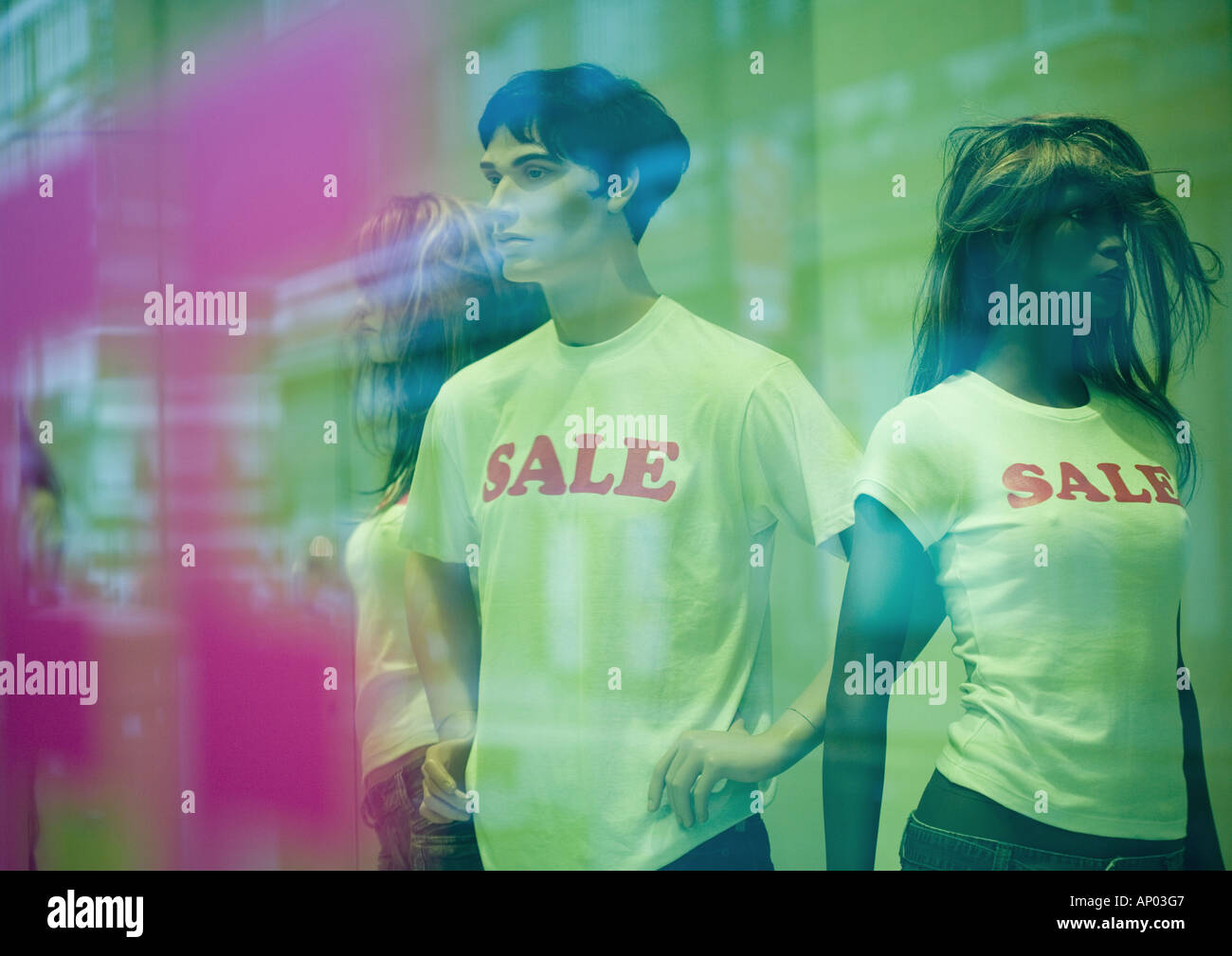 Mannequins in shop window wearing sale tee-shirts - Stock Image