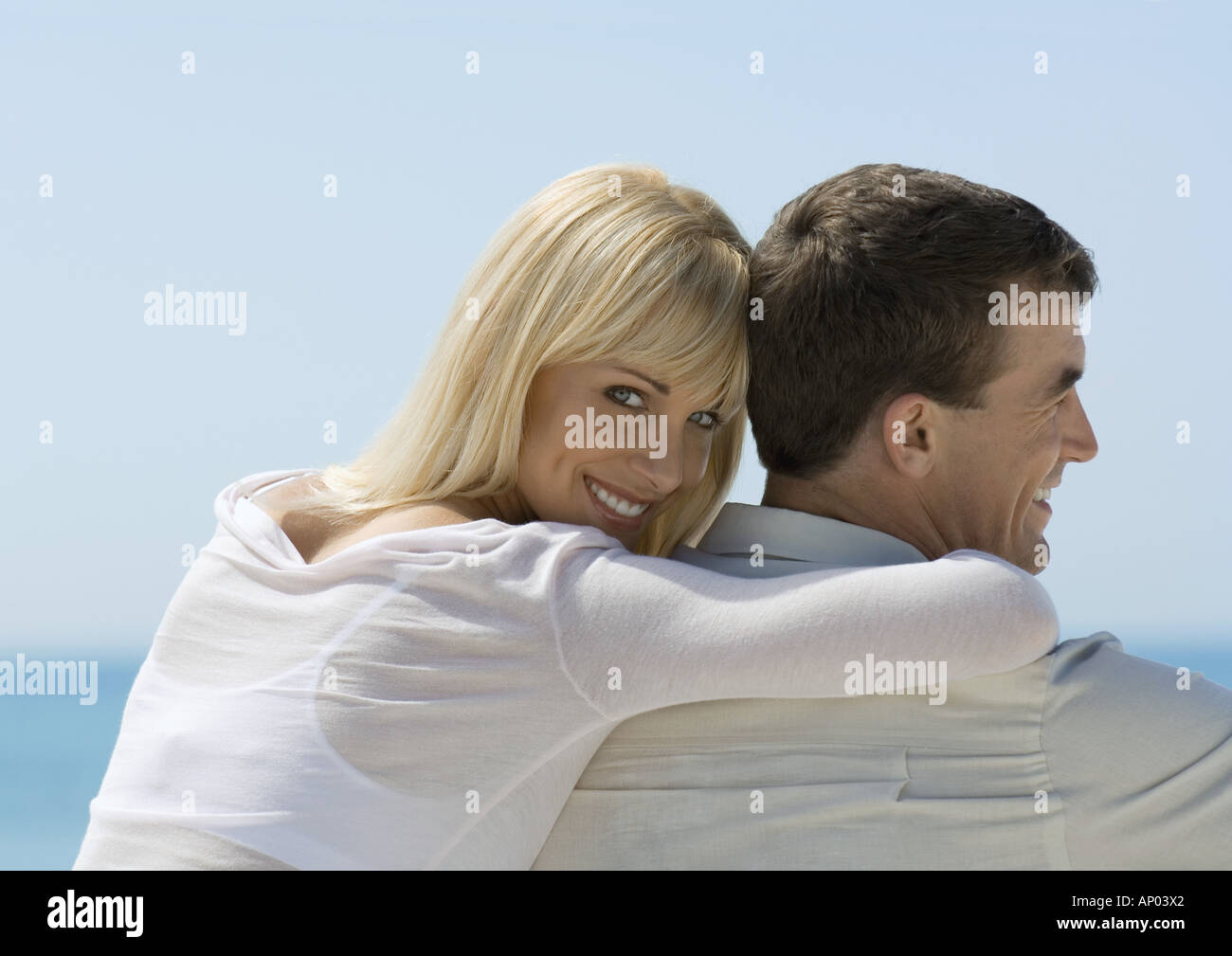 Woman leaning against man, looking over shoulder at camera, sea in background - Stock Image