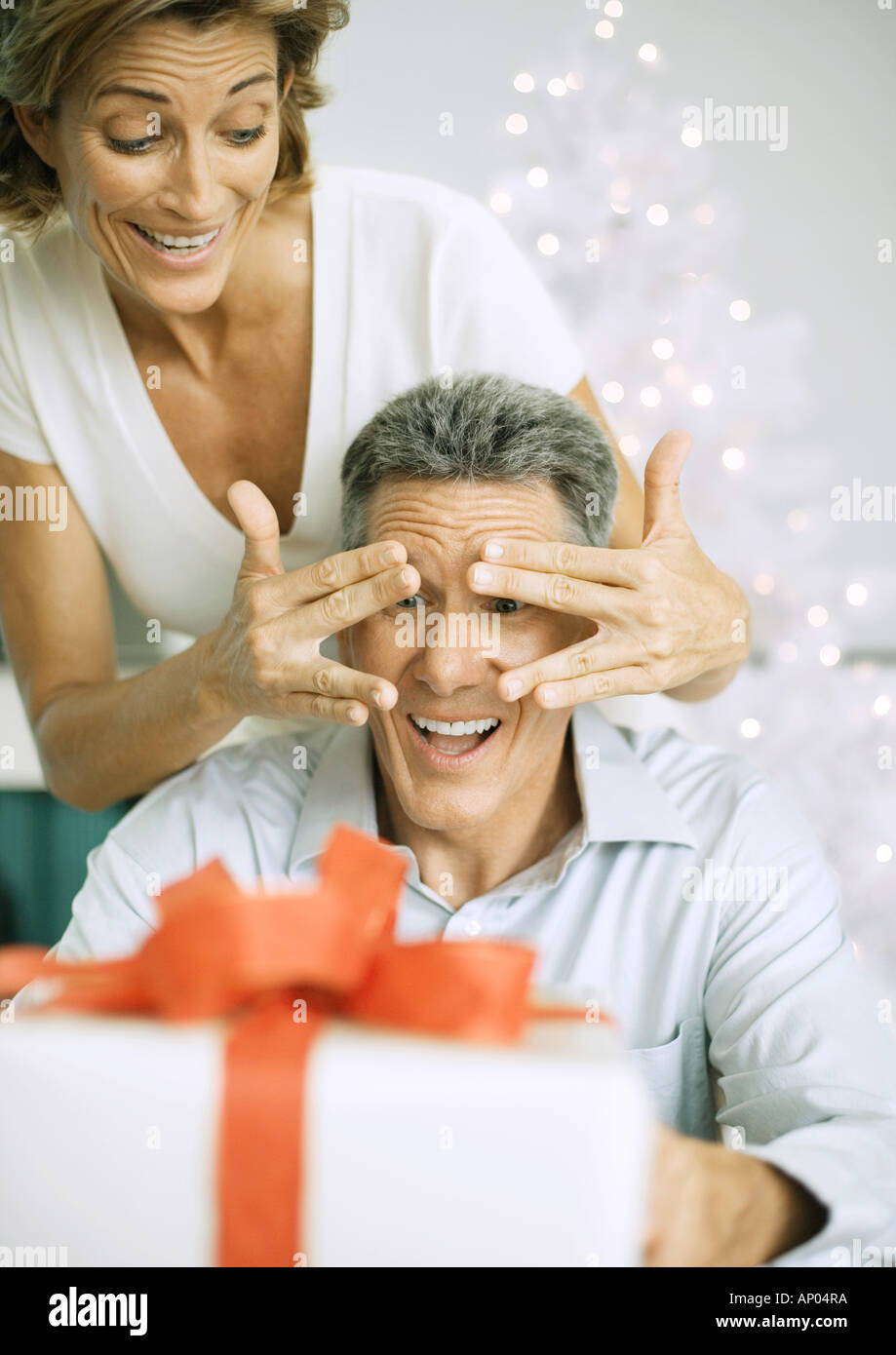 Woman surprising husband with christmas present - Stock Image