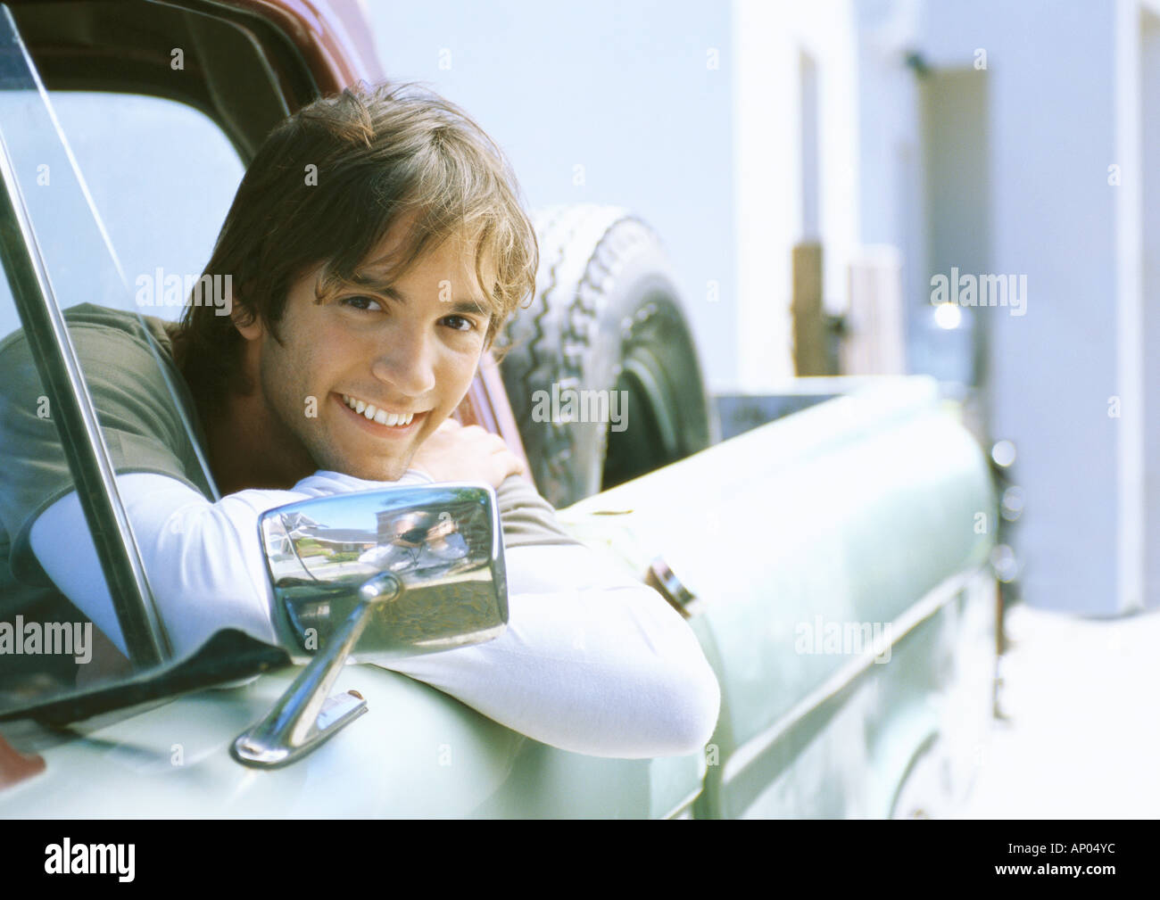 Young man in car, leaning on edge of car window frame - Stock Image