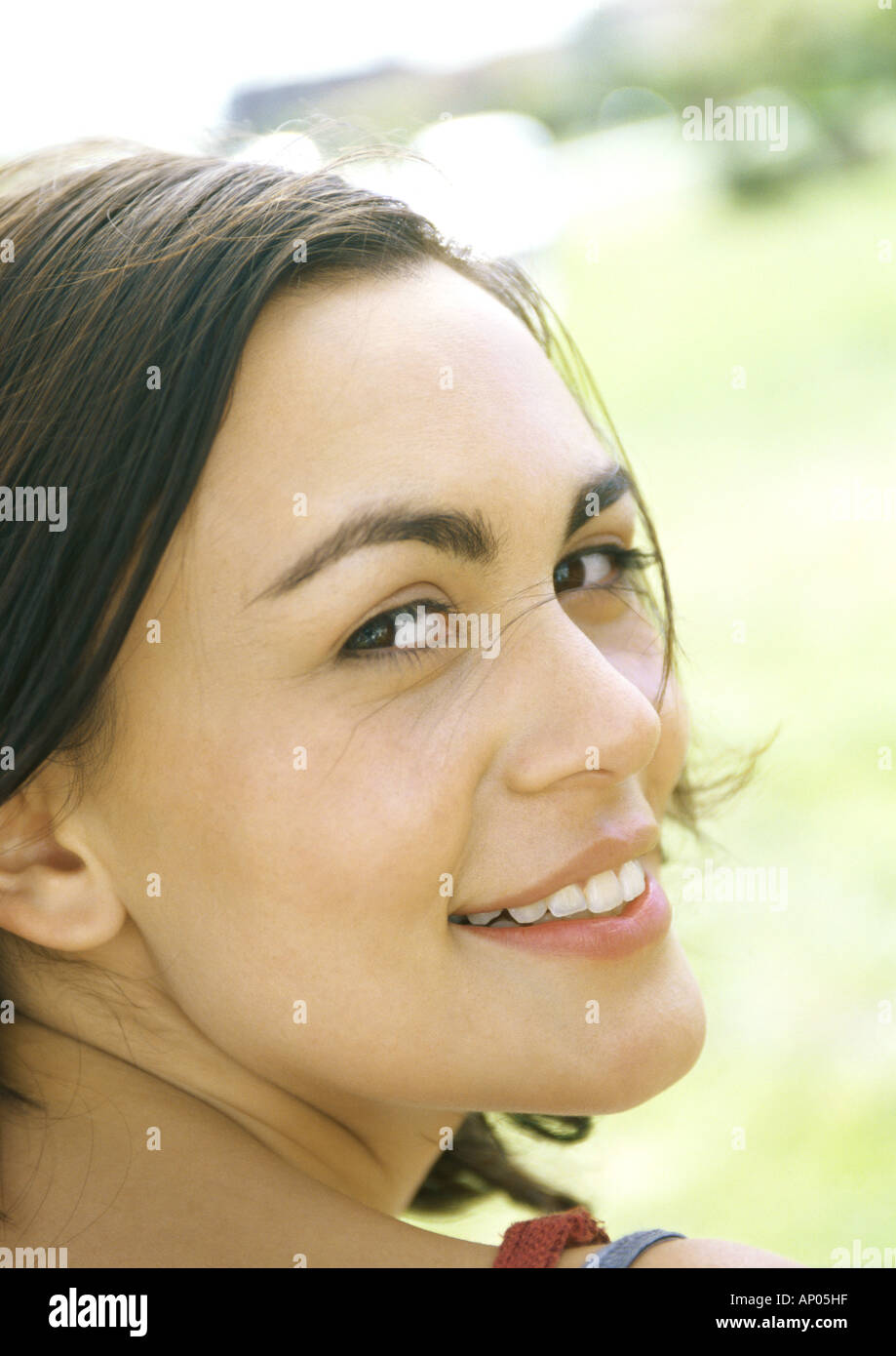 Young woman, looking over shoulder, smiling at camera Stock Photo