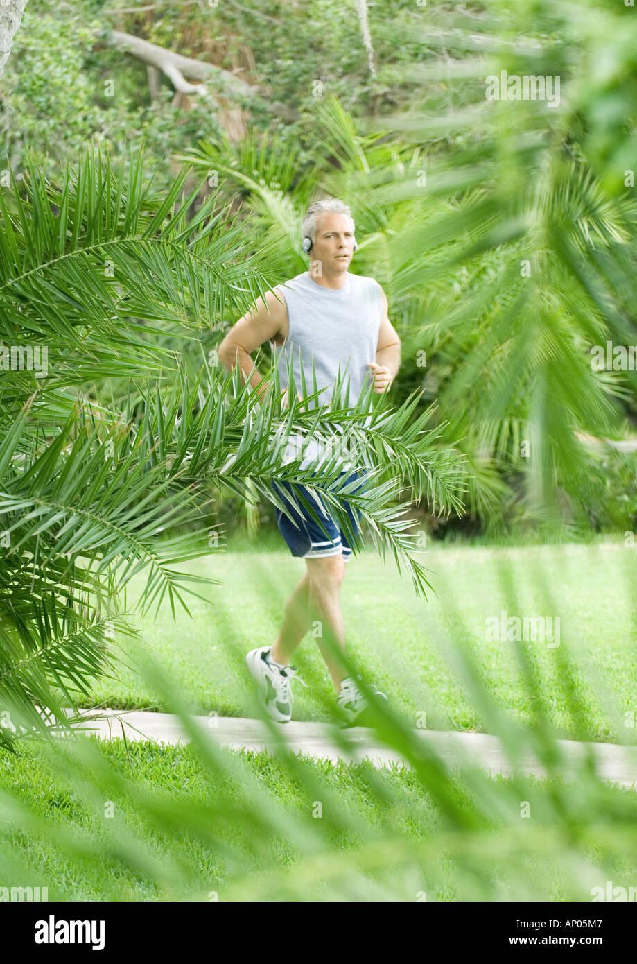 Mature man jogging on walkway - Stock Image