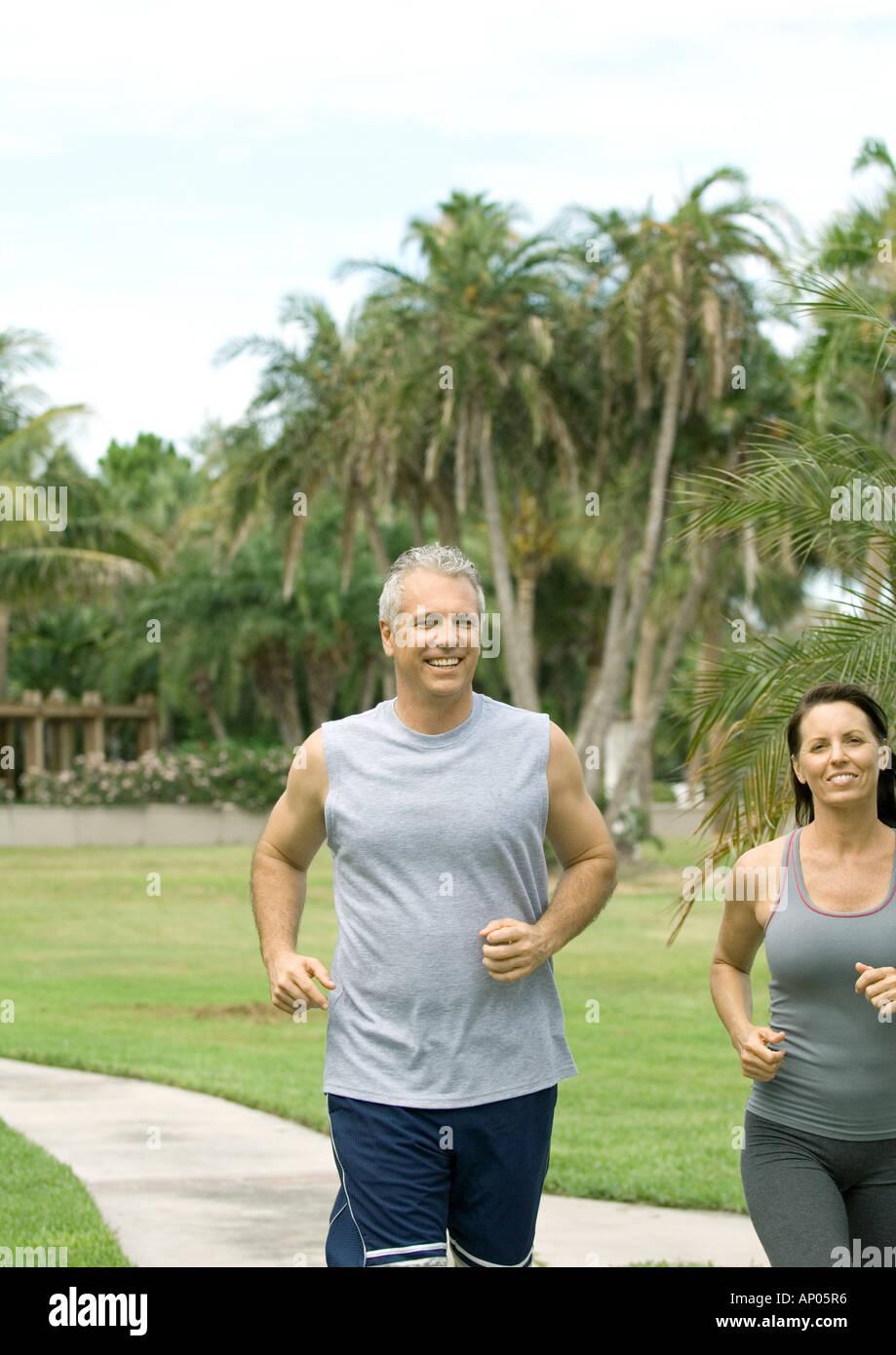 Mature couple running on walkway - Stock Image