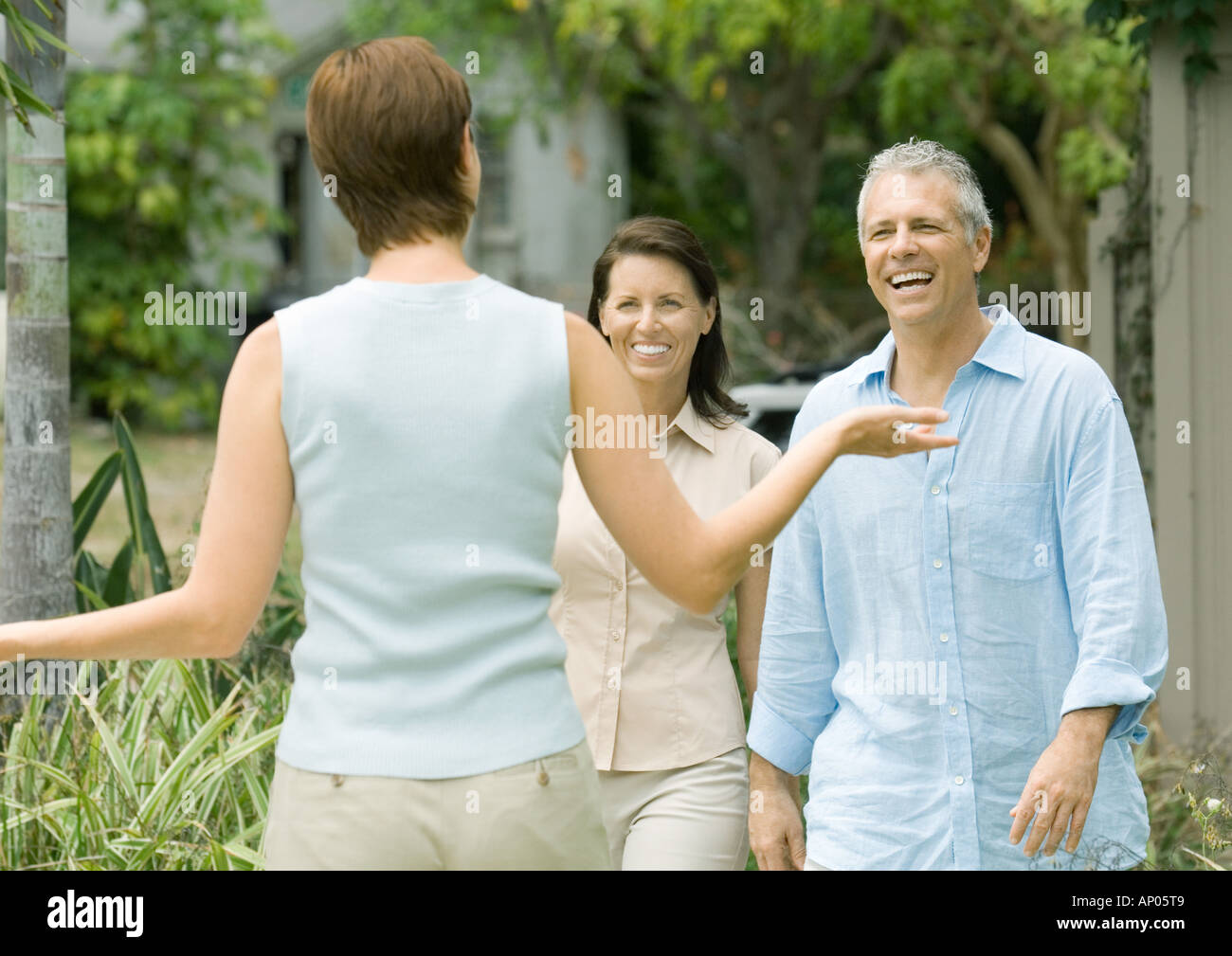 Woman greeting mature couple - Stock Image