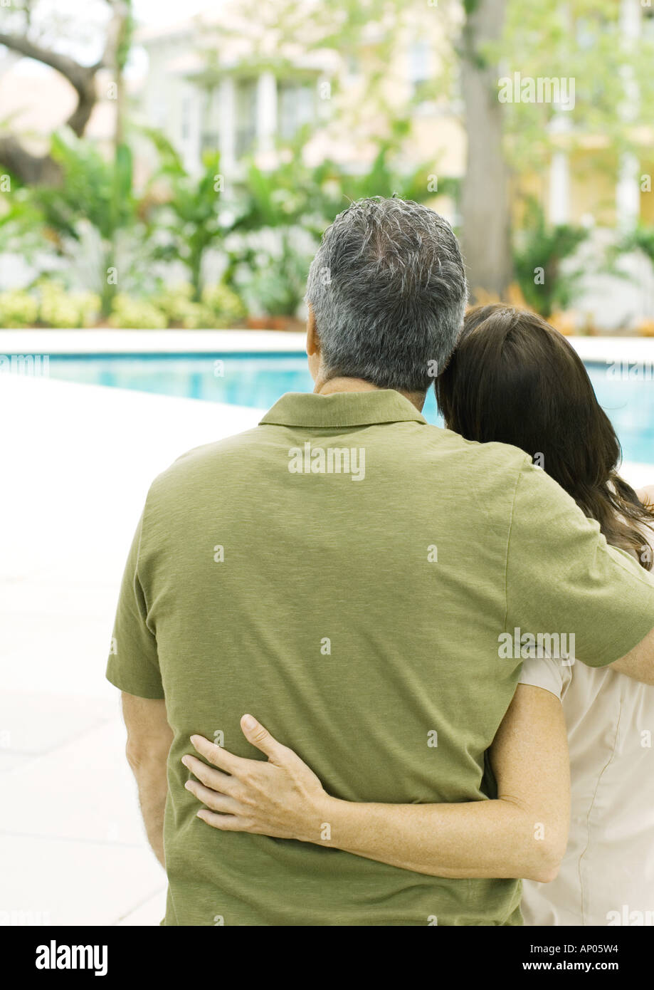 Couple standing with arms around each other, looking at swimming pool Stock Photo