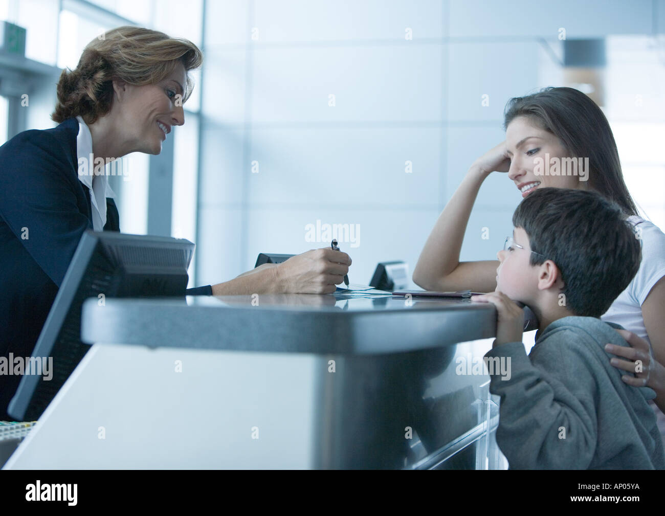 Woman and son standing at check-in counter in airport - Stock Image