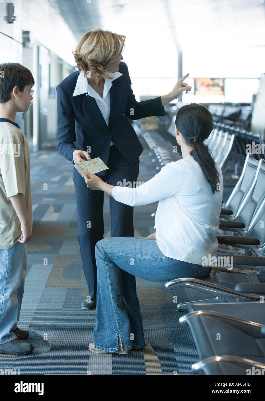 Female traveler showing ticket to airline attendant - Stock Image