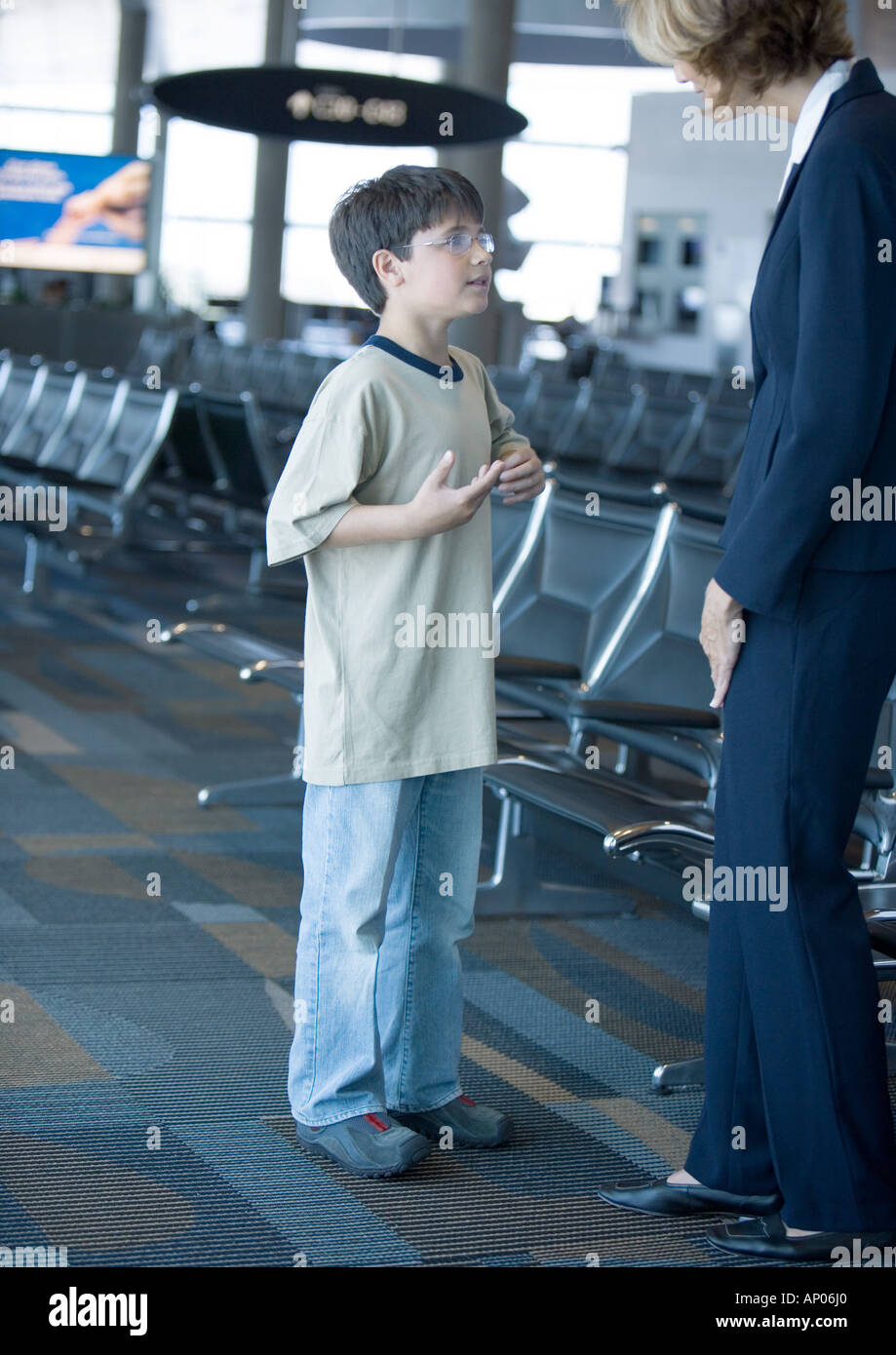 Boy speaking to airline attendant in airport lounge - Stock Image