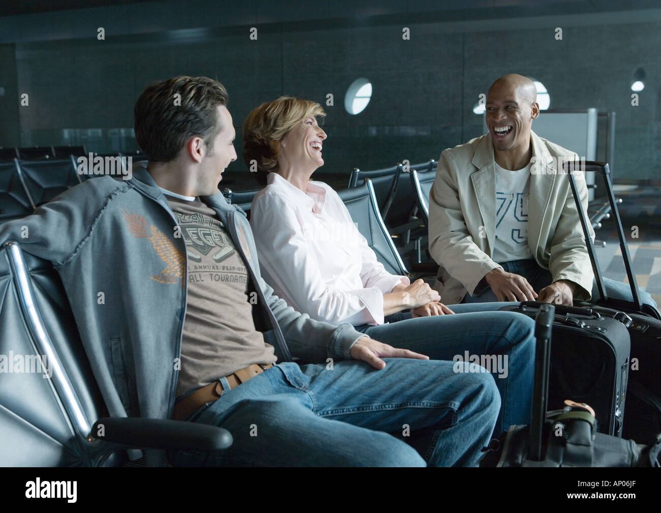 Travelers chatting in airport lounge - Stock Image