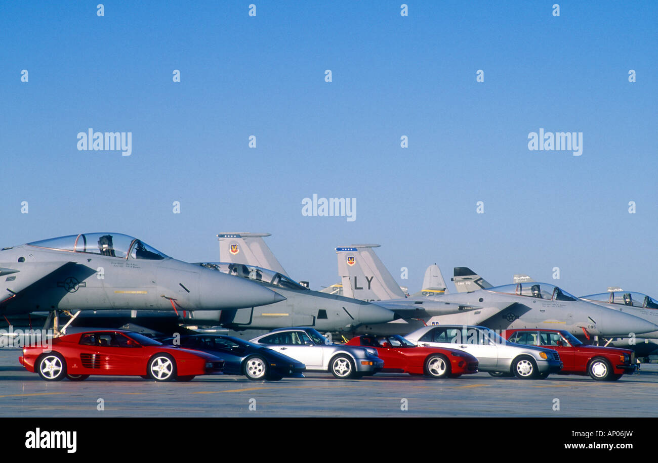 Group of 1980's luxury cars parked with F16 fighter jets. - Stock Image
