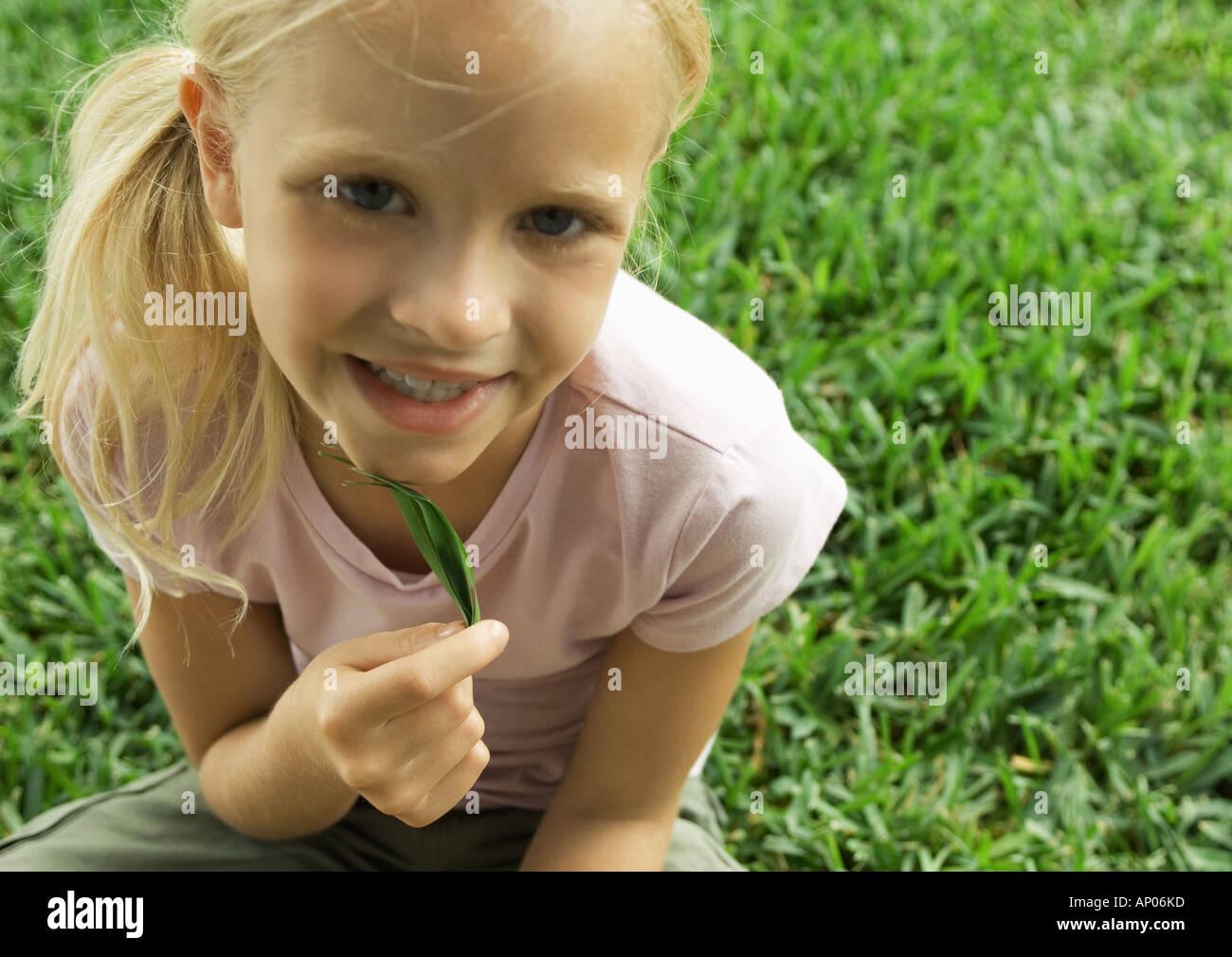 Girl holding leaf under chin - Stock Image