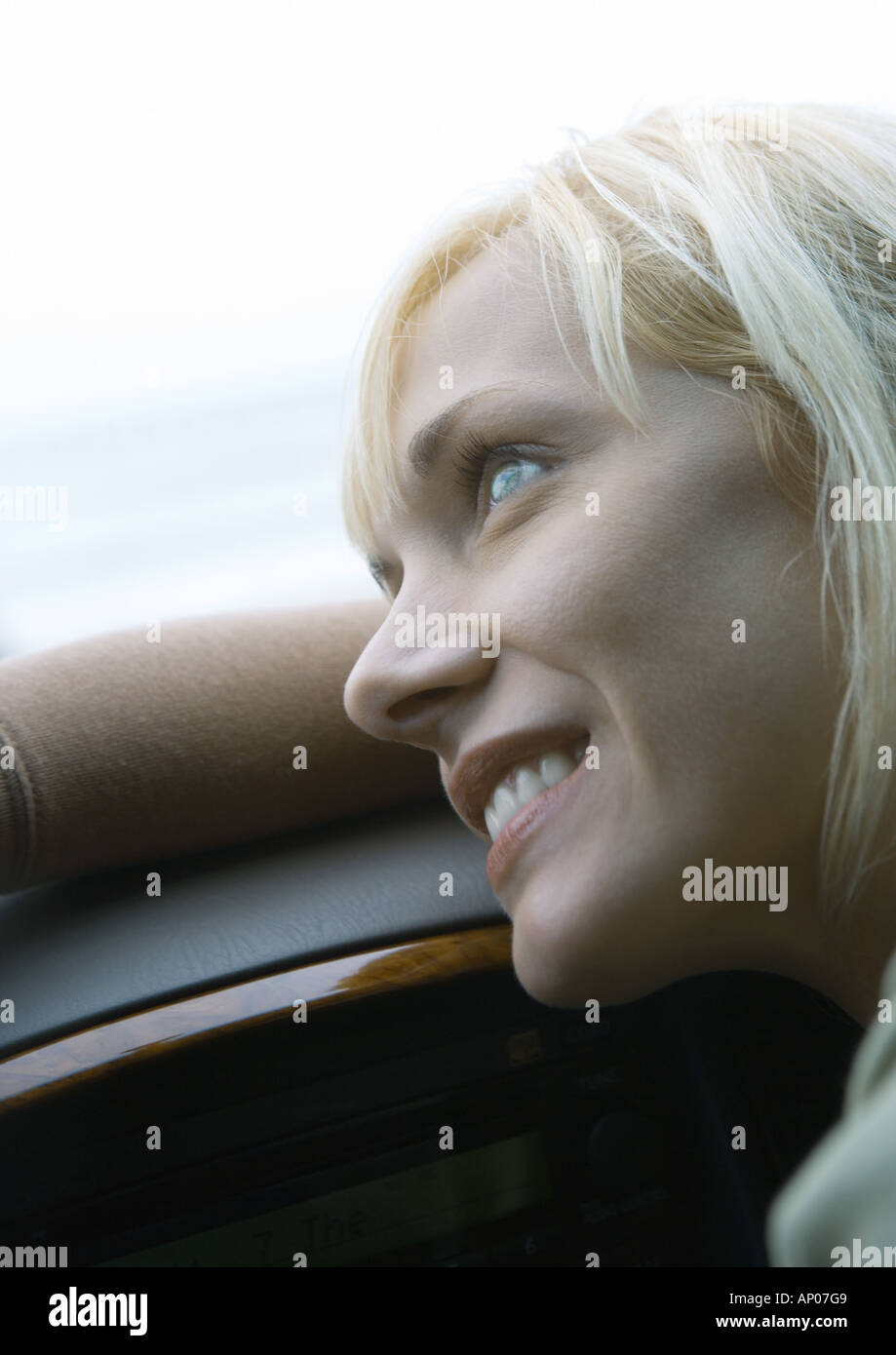 Woman leaning head on dashboard - Stock Image