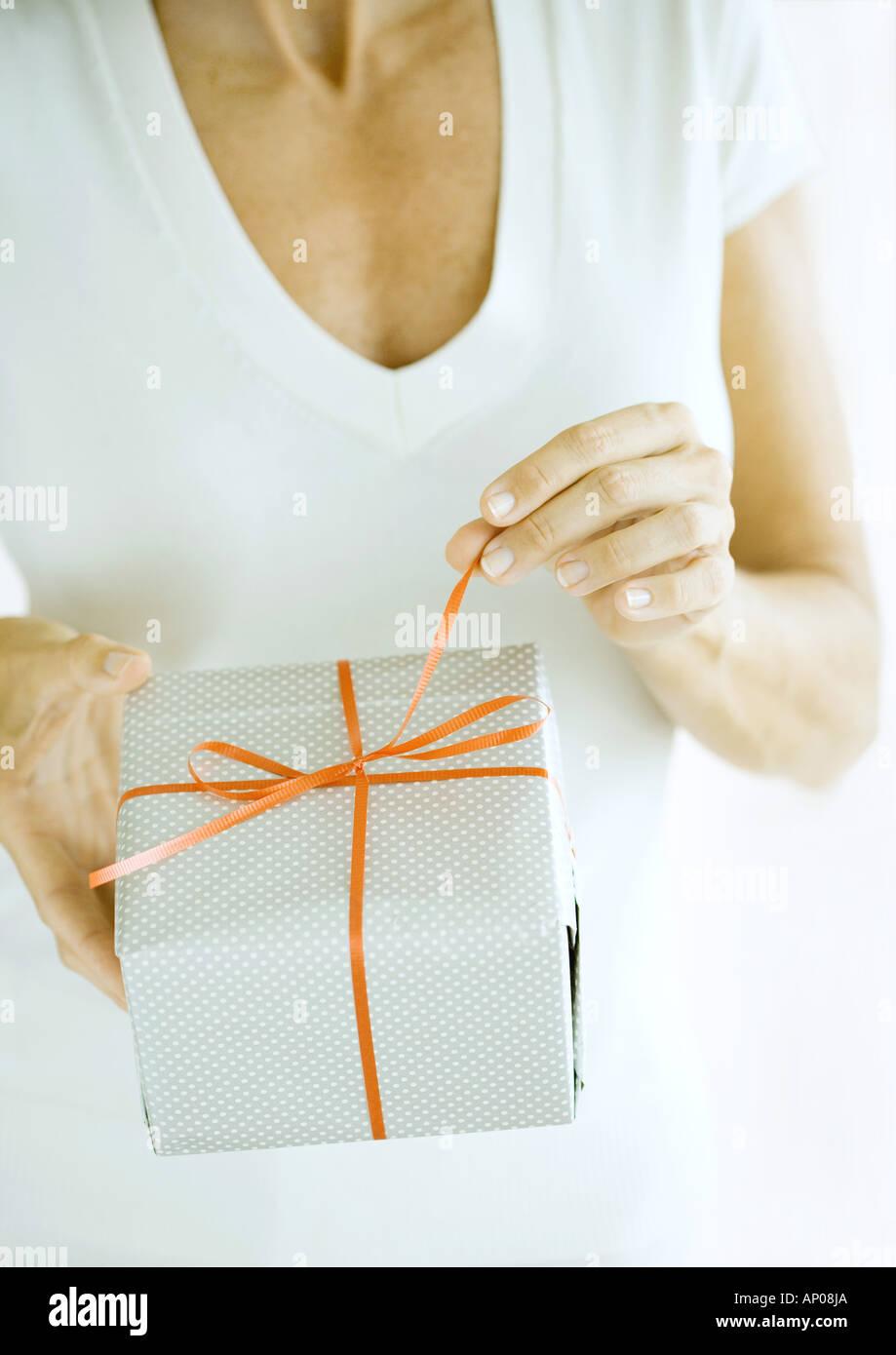 Woman pulling ribbon on present - Stock Image