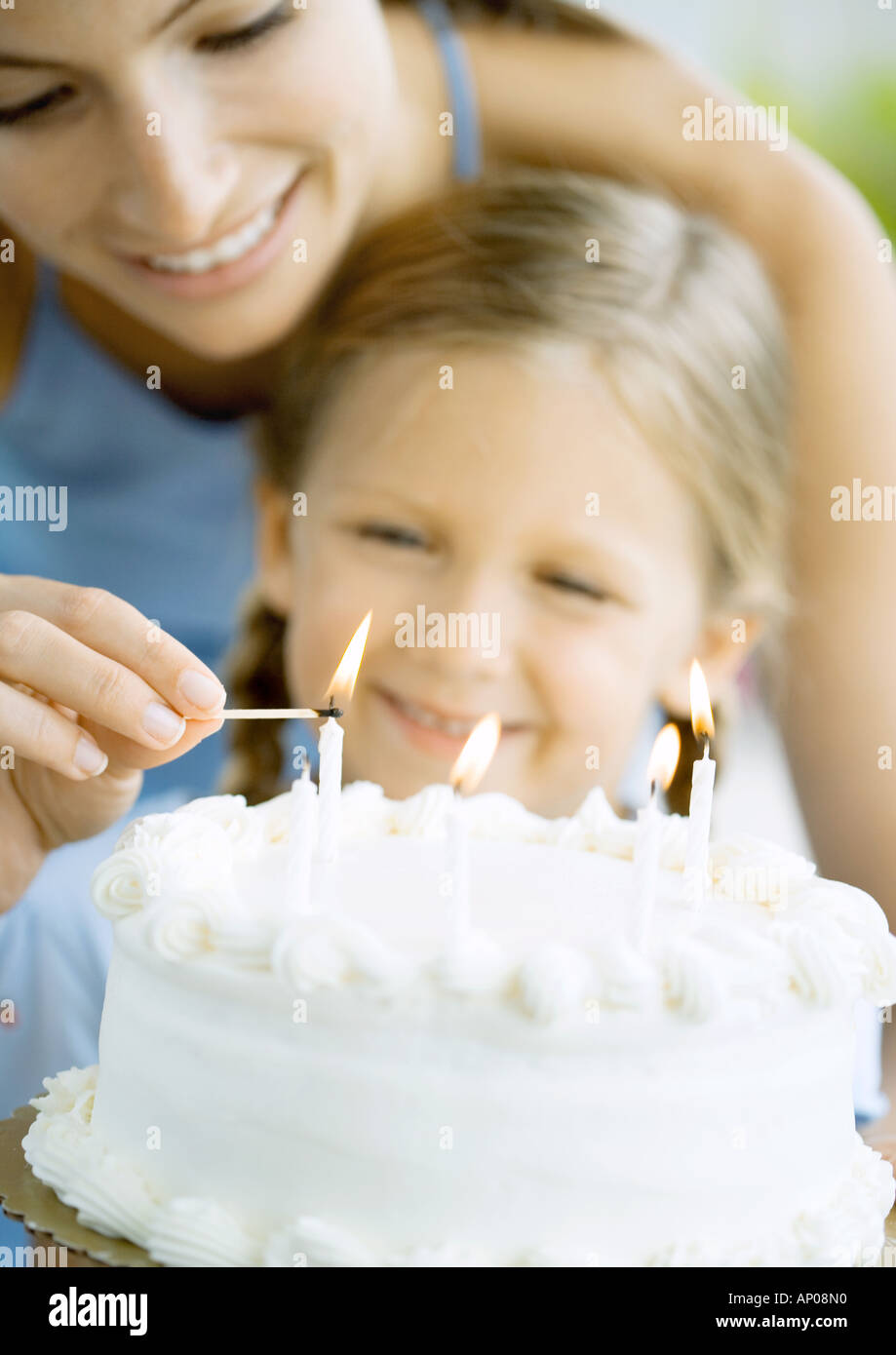 mother lighting candles on birthday cake for daughter stock photo