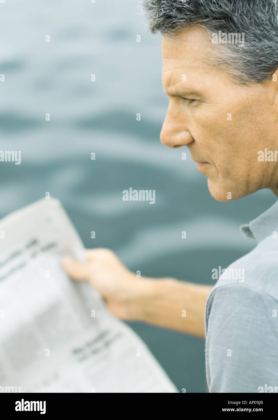 Man holding newspaper, looking away - Stock Image