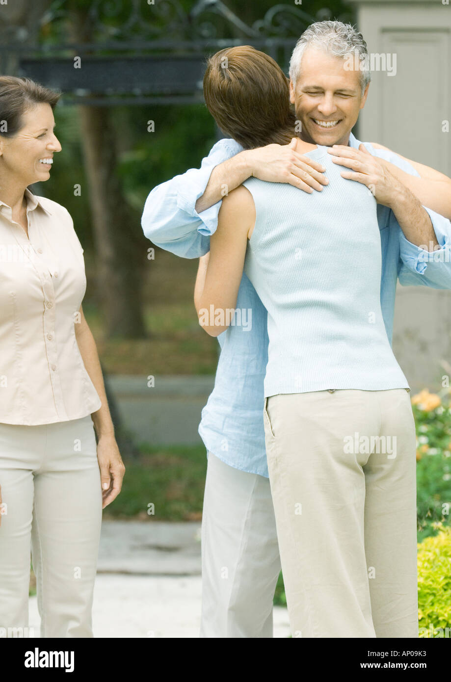 Woman hugging man as second woman watches smiling - Stock Image