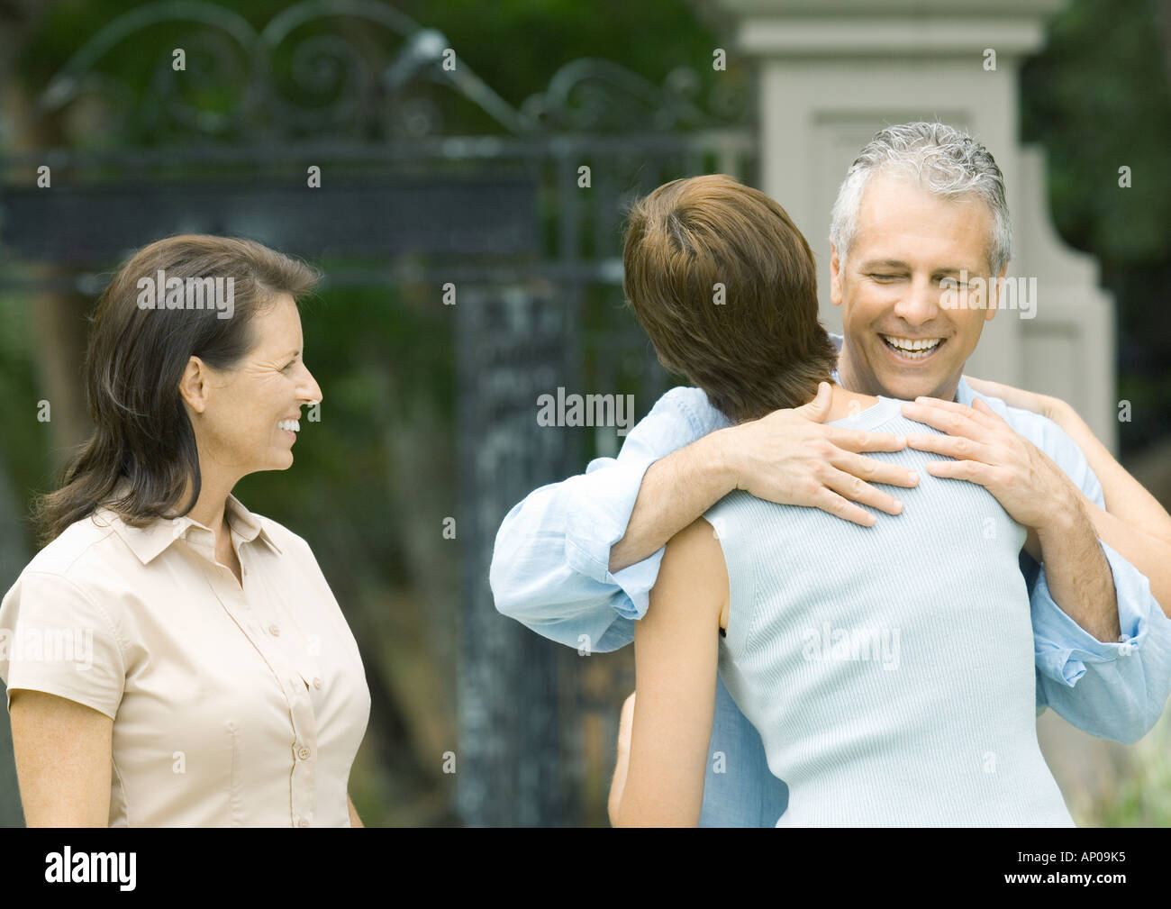 Woman hugging man as second woman watches, smiling - Stock Image