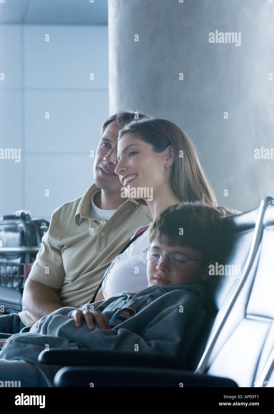 Family sitting in airport lounge, boy sleeping Stock Photo