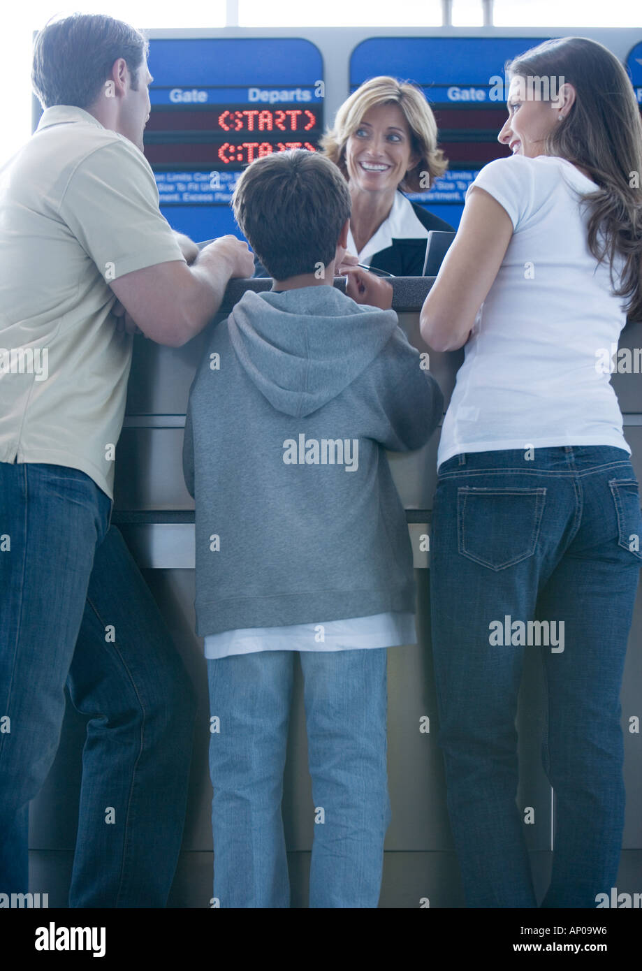 Family standing at airline check-in counter - Stock Image
