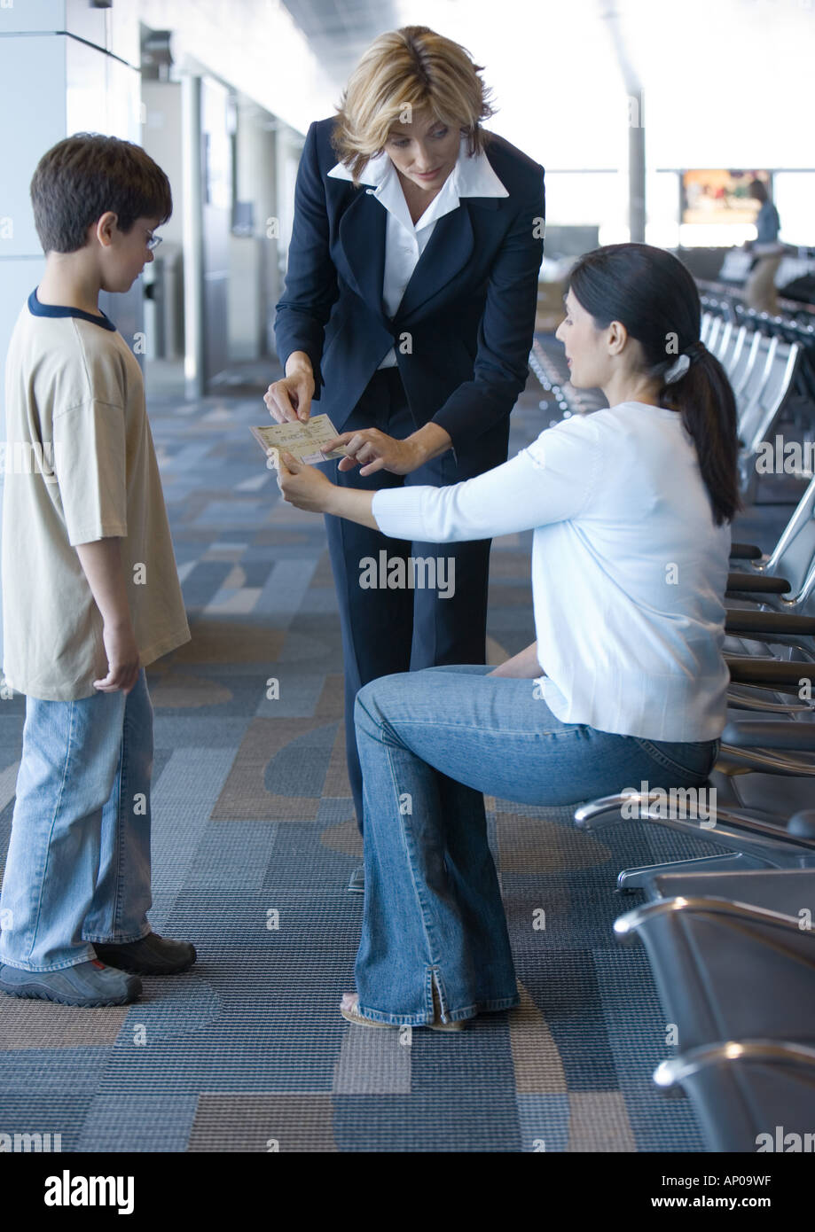 Airline attendant helping travelers - Stock Image