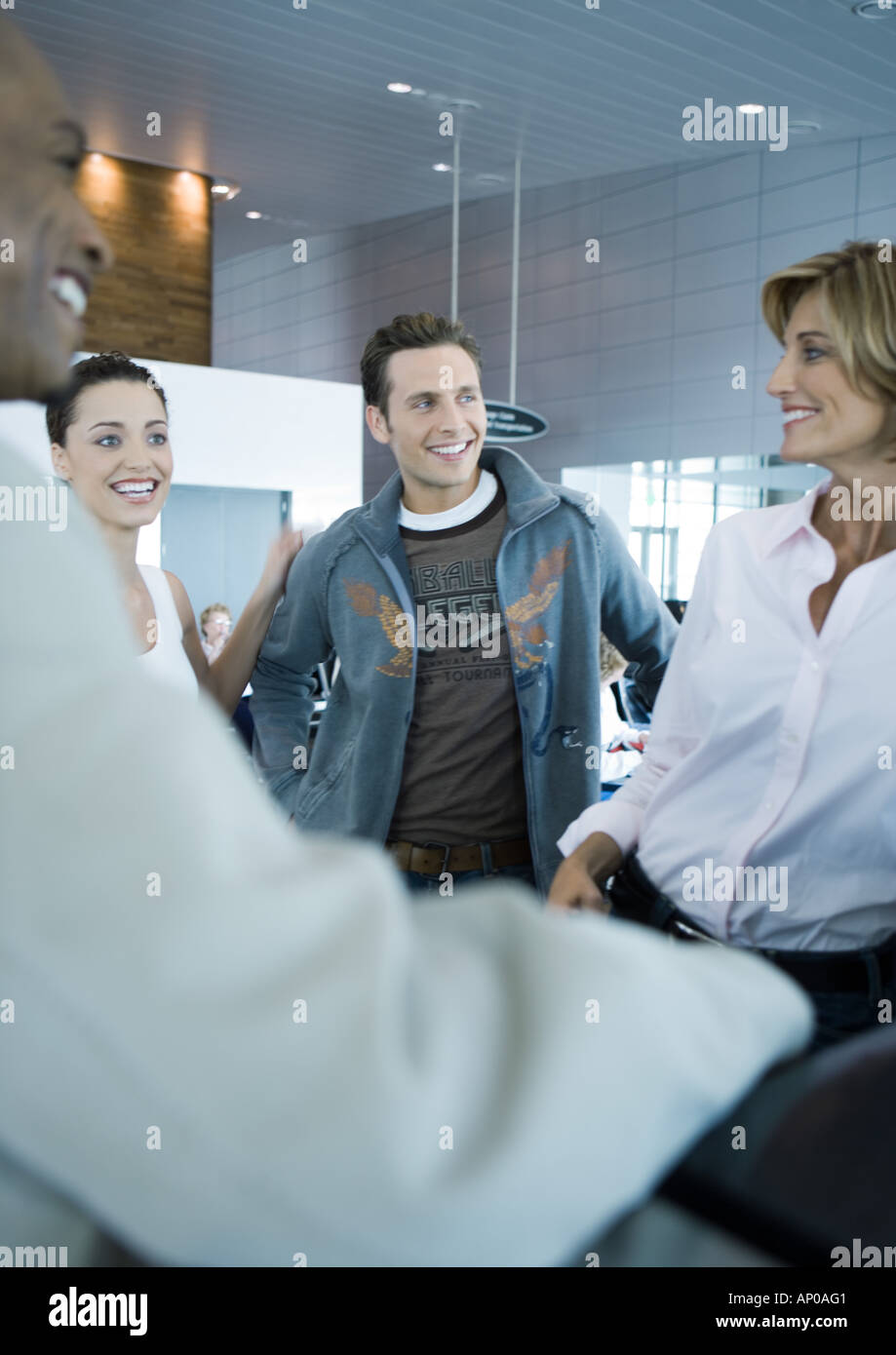 Group of people standing, smiling, in boarding area of airport - Stock Image