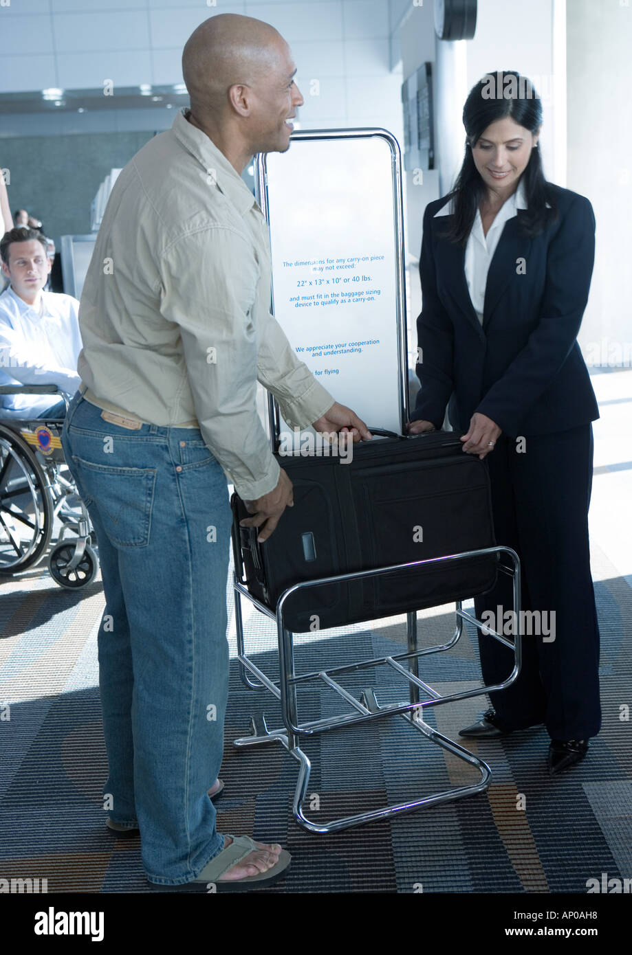 Man checking dimensions of carry-on bag at boarding gate - Stock Image