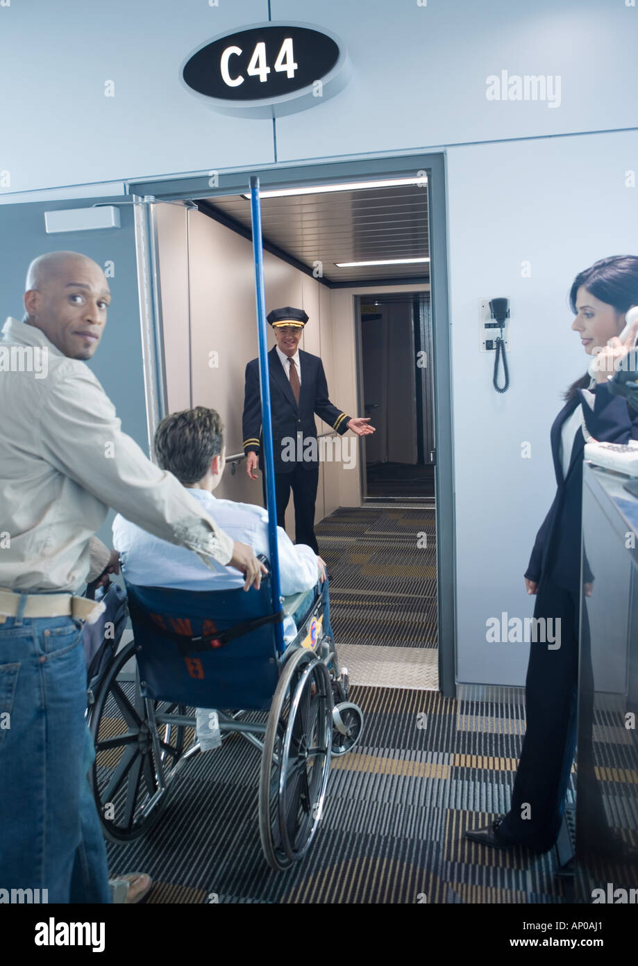 Man with traveler in wheelchair at boarding gate - Stock Image