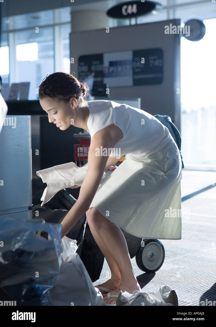 Woman bending over, looking through bags, in airport - Stock Image