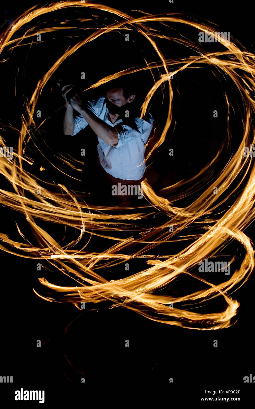 Man Fire dancing with fire sticks at night. India. Abstract Pattern. Long Exposure - Stock Image