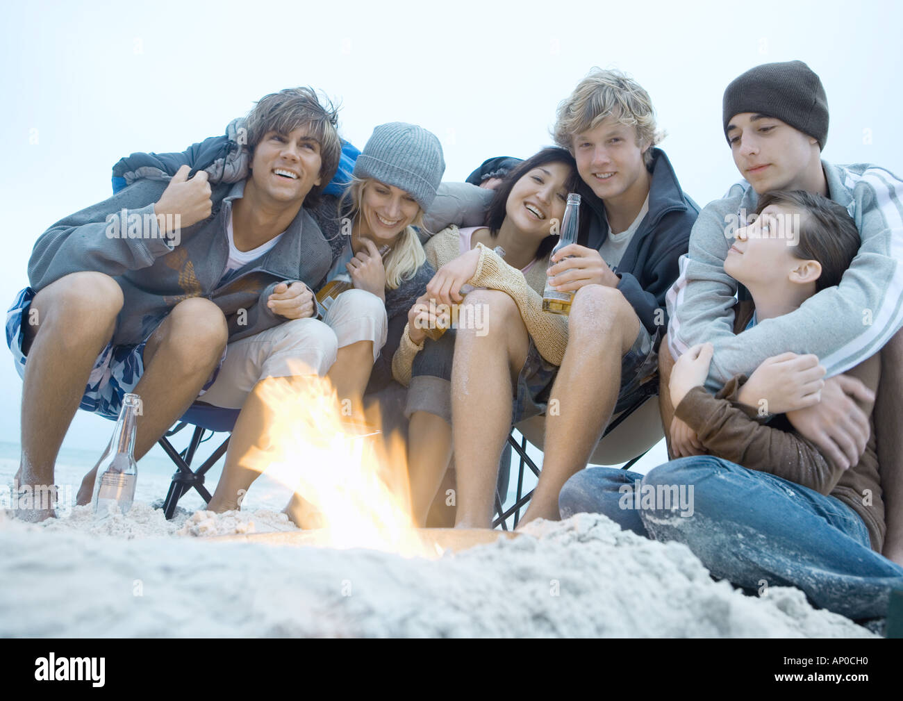 Group of friends sitting around campfire - Stock Image