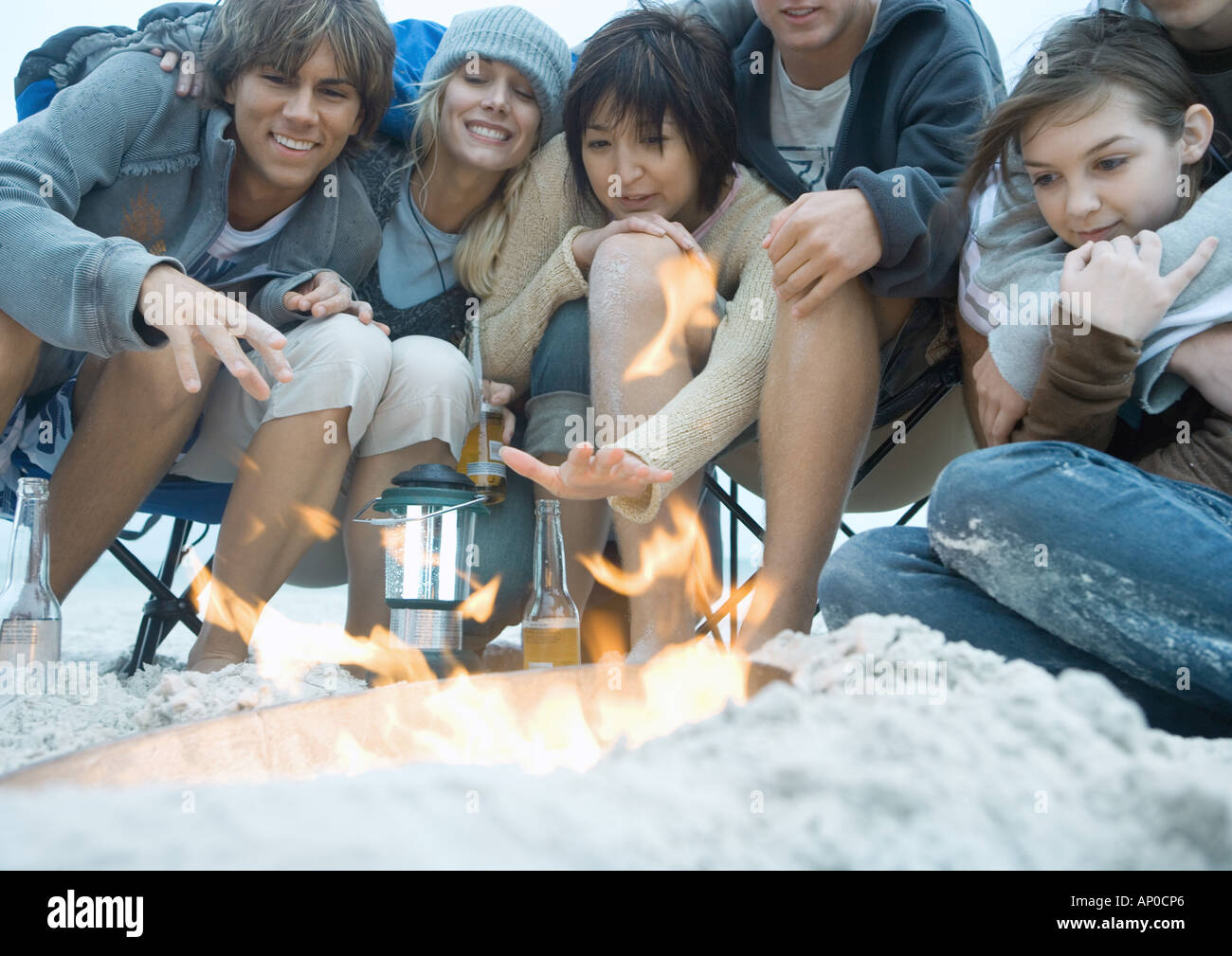 Group of young adult friends, sitting around campfire on beach, reaching hands toward fire - Stock Image