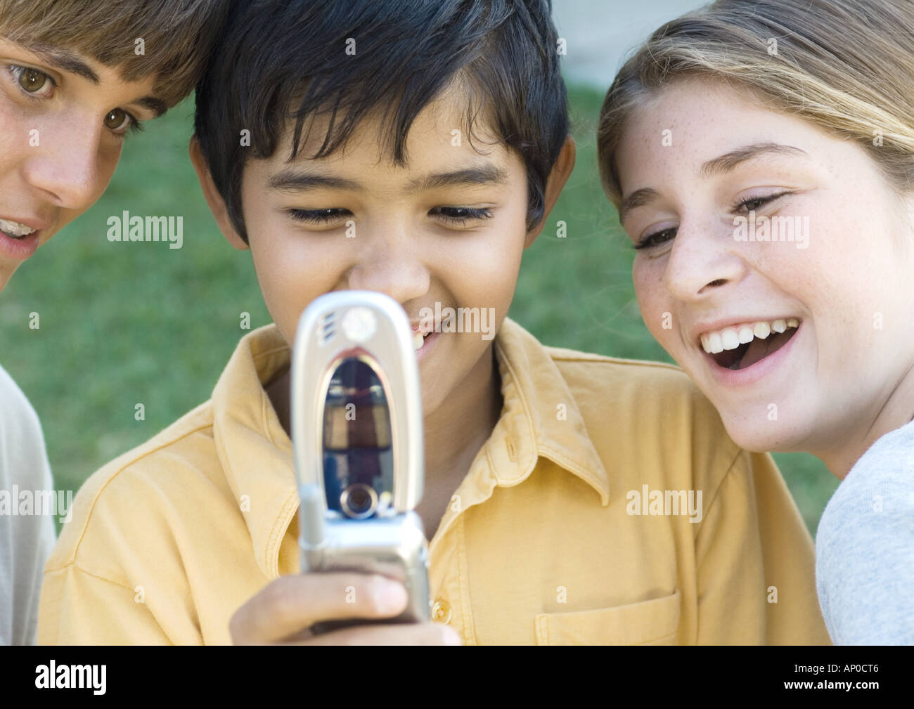Three preteen kids looking at cell phone - Stock Image