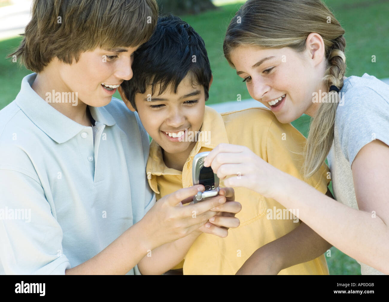 Three preteen friends looking at cell phone - Stock Image