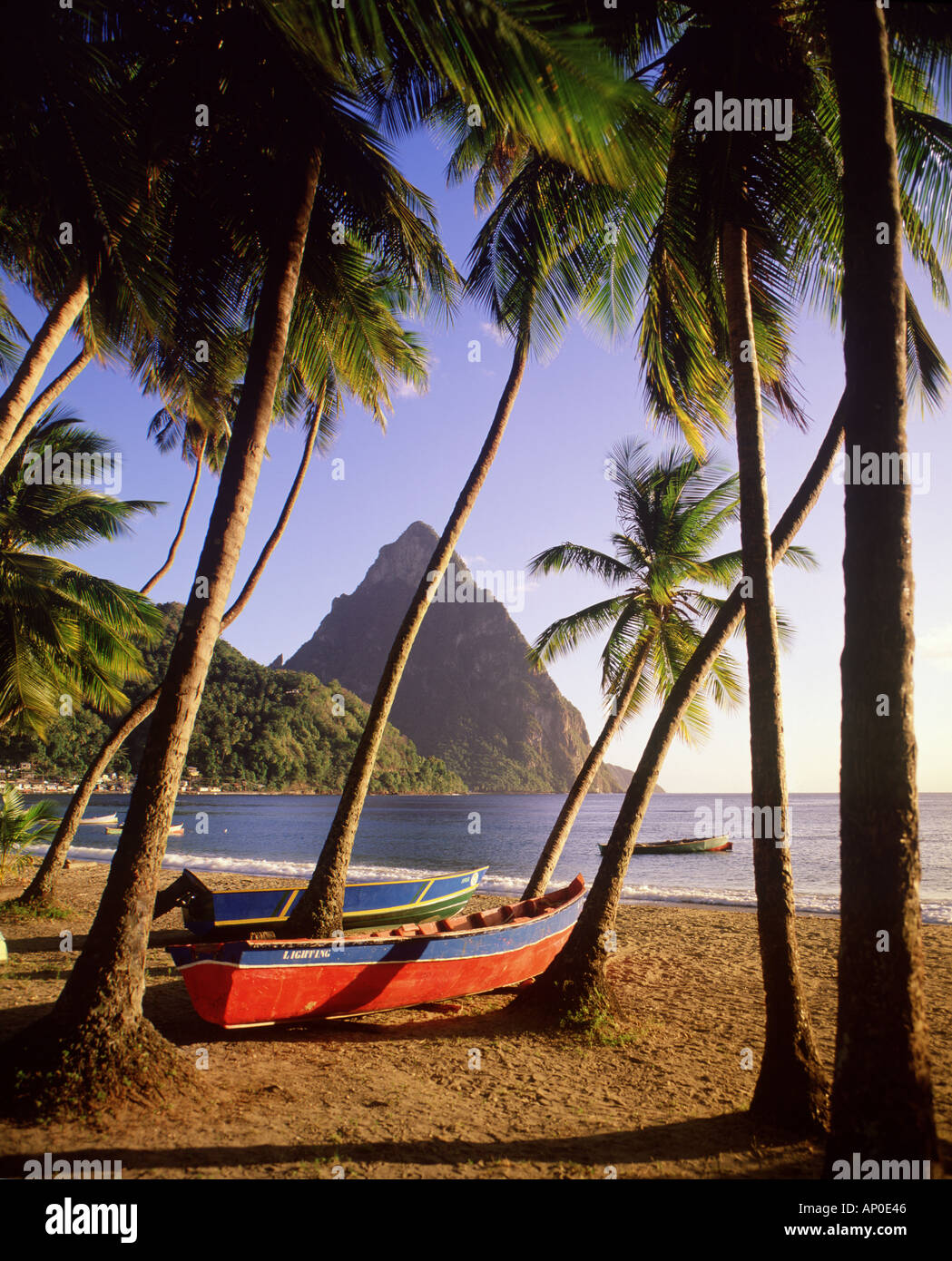 The Pitons tower above Soufriere beach on the Caribbean island of St Lucia as fishing boats lay on the beach below the towering - Stock Image