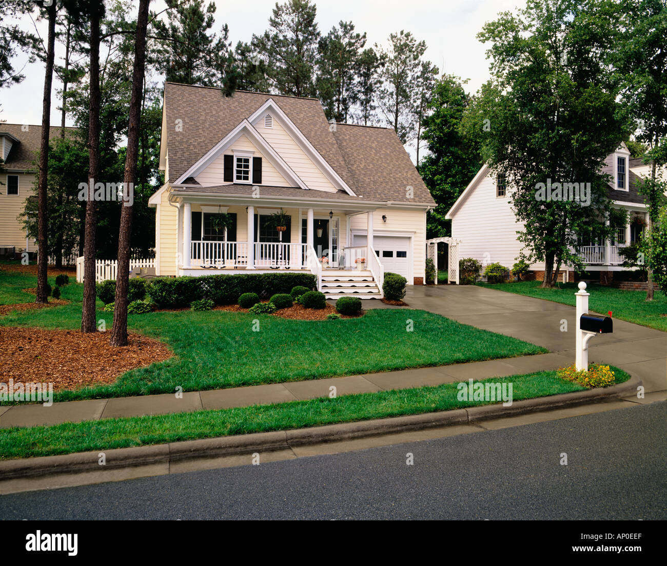 Small Two Story Cream House With Black Shutters White Trim