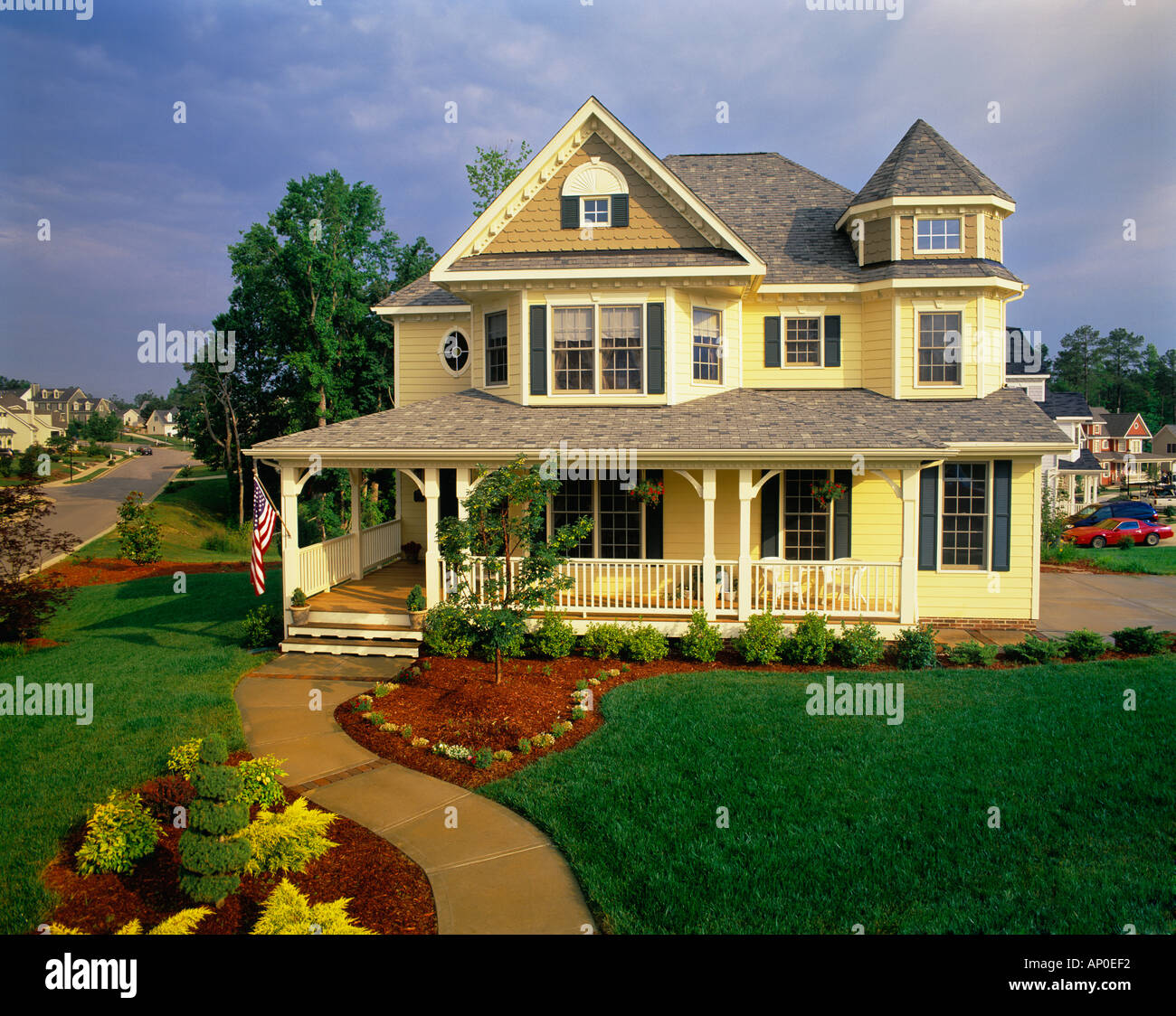 Large Two Story Yellow Victorian House With Blue Shutters And A Large Porch - Stock Image