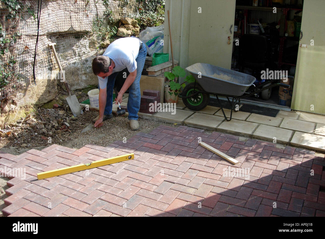 A Construction Worker Laying A Patio Using Block Paving Bricks