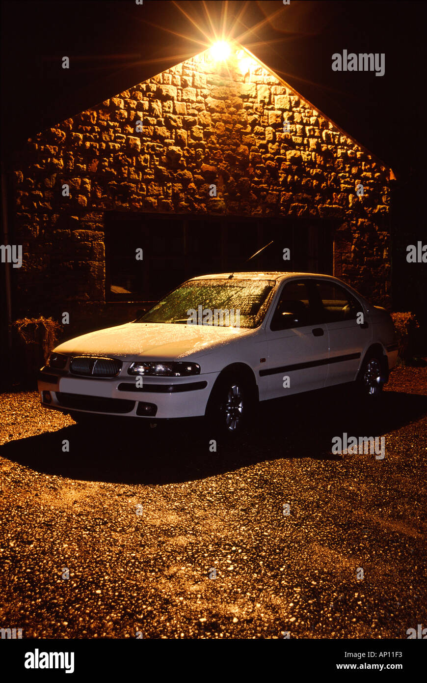 Car On A Driveway At Night Lit By A Security Light Stock Photo