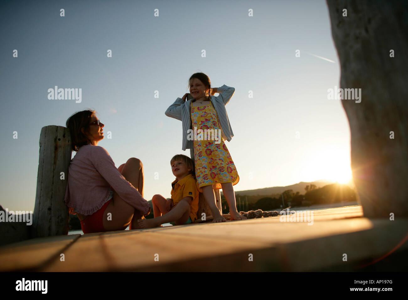Family sitting on jetty, Santa Giulia Beach, Southern  Corse, France - Stock Image