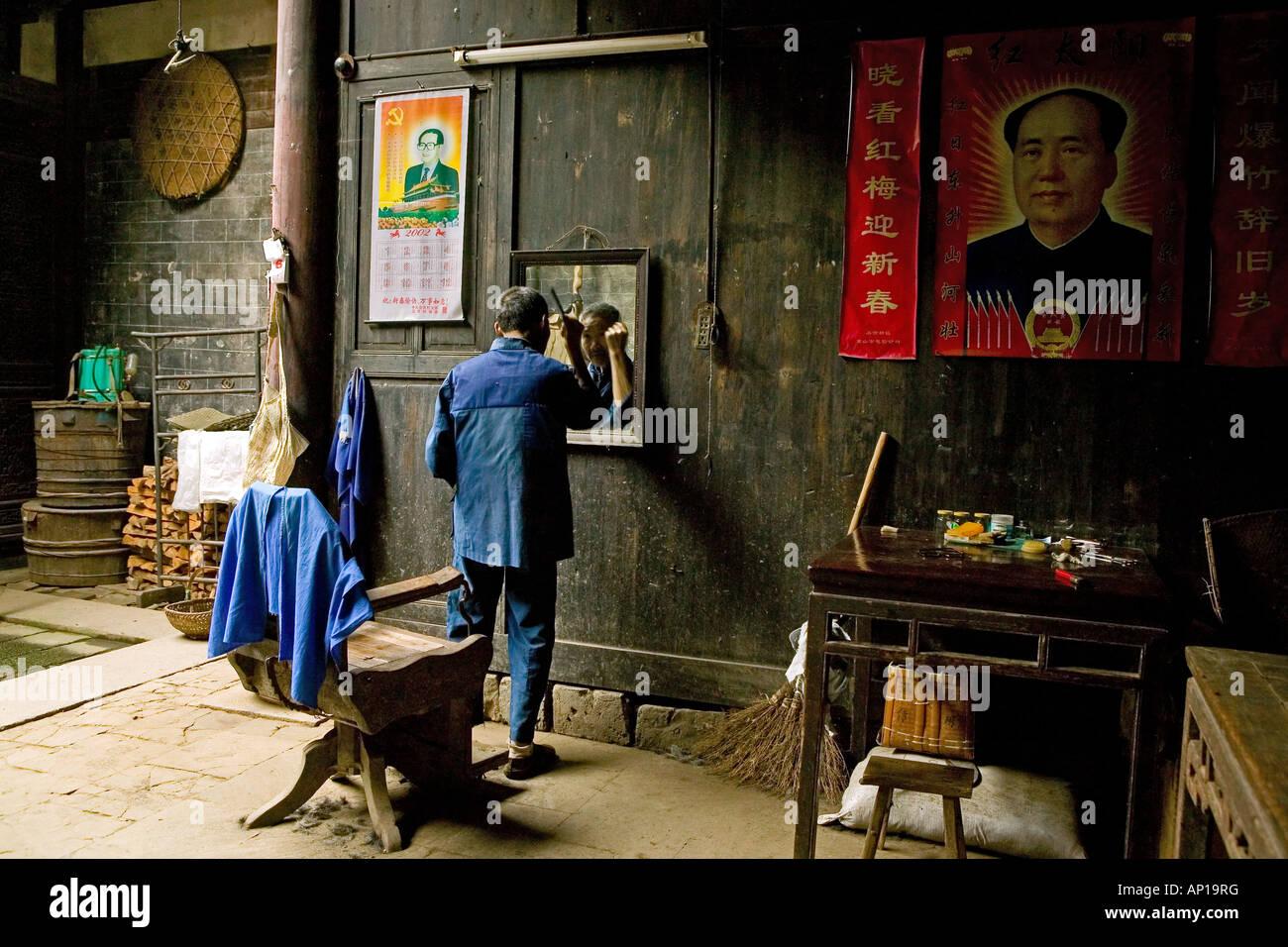 village barber, Mao portrait, courtyard of timber house in Chengkan, ancient village, living museum, Chengkan near - Stock Image