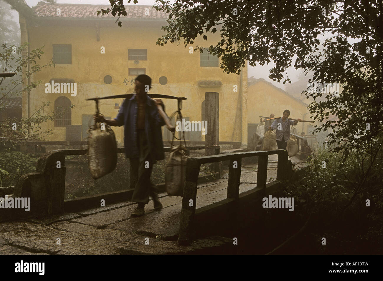 Porters carrying building material in front of Tianchi monastery at the village Jiuhuashan, Anhui province, China, - Stock Image