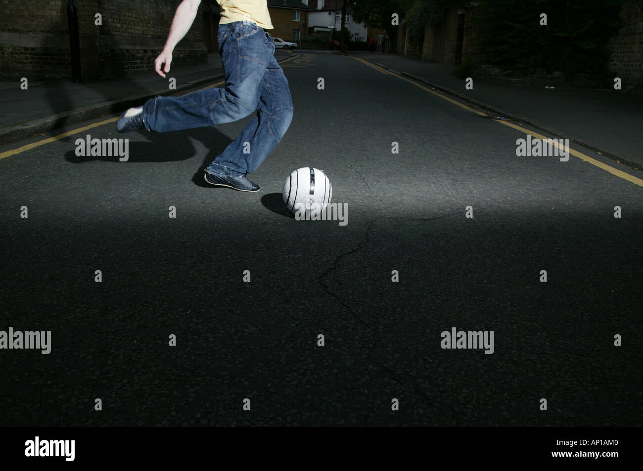 Man Kicking A Football At Night   Stock Image