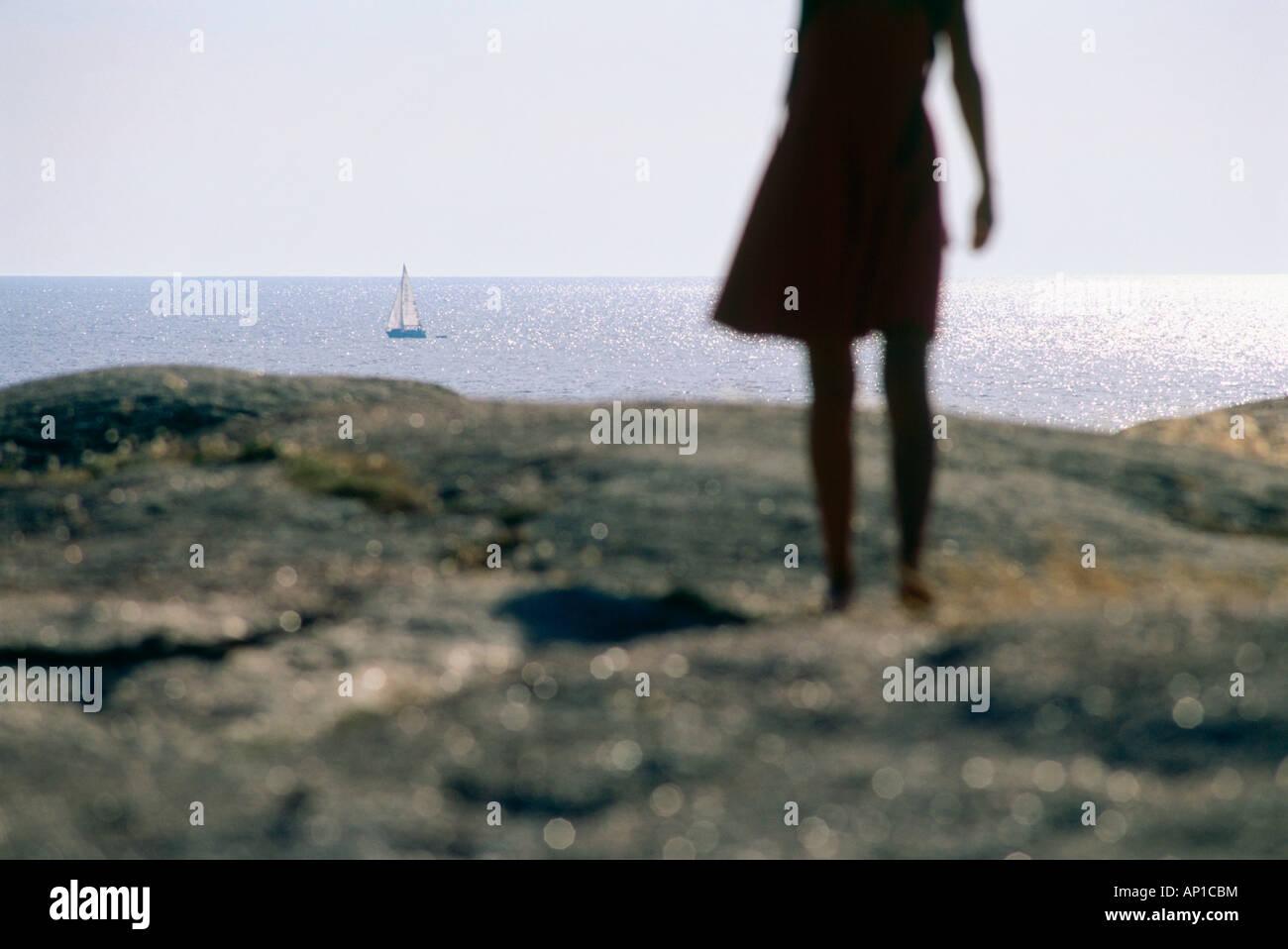 Woman standing on granite rock looking out on sea, Smoegen, Bohuslan, Sweden - Stock Image