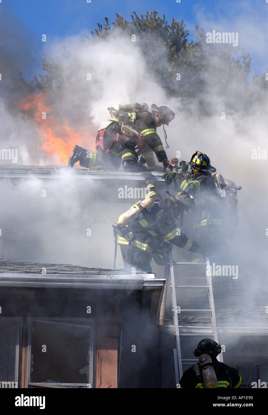 Firefighters scramble off the roof during a fire House fire in New Haven CT as the flames go out of control - Stock Image